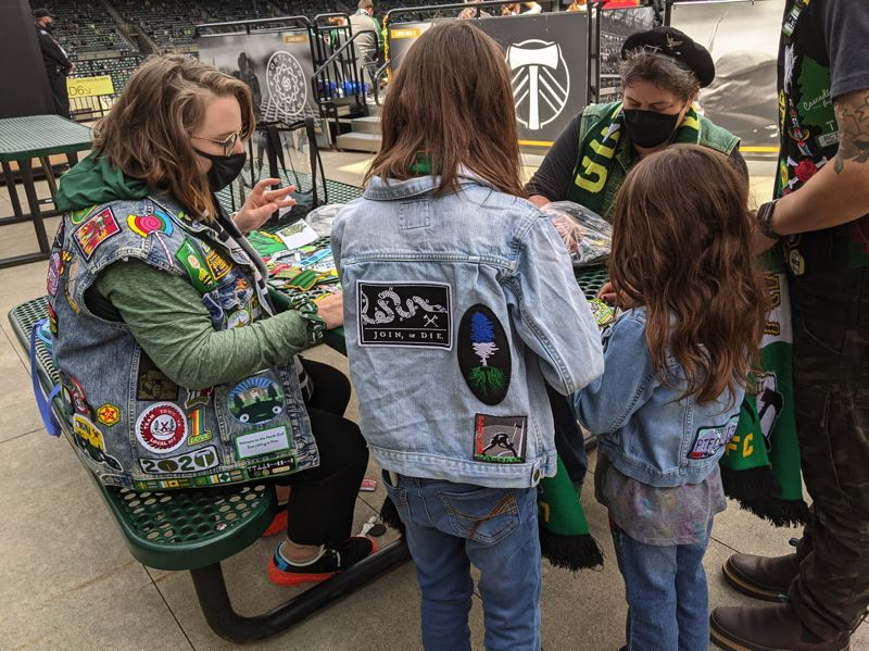 PAMPLIN MEDIA GROUP: JOSEPH GALLIVAN - The Patch Patrol stays busy in the second half on the South End. A dad brought his daughters to swap patches.