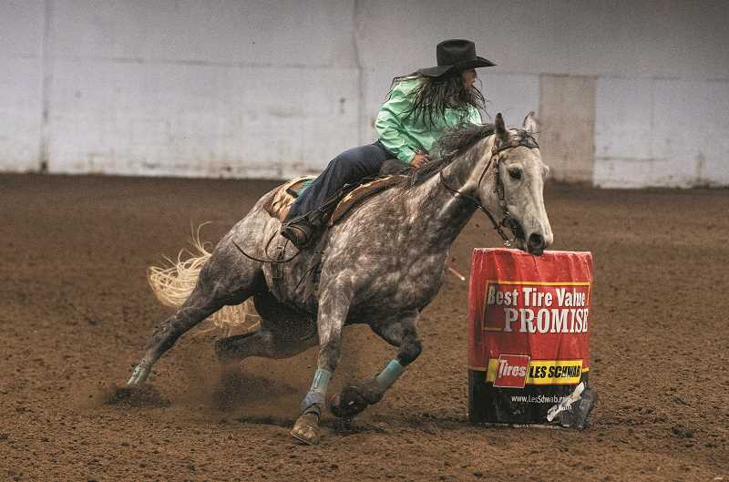 LON AUSTIN/CENTRAL OREGONIAN - Crook County's Gracie Flitner flies around a barrel on her mount for the Central Oregon Team. She took fifth in the first go round in the barrels.