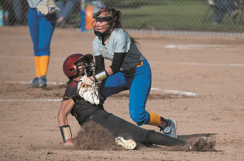 LON AUSTIN/CENTRAL OREGONIAN - Danner Hemphill appplies the tag during the Cowgirls' 10-8 win over The Dalles.