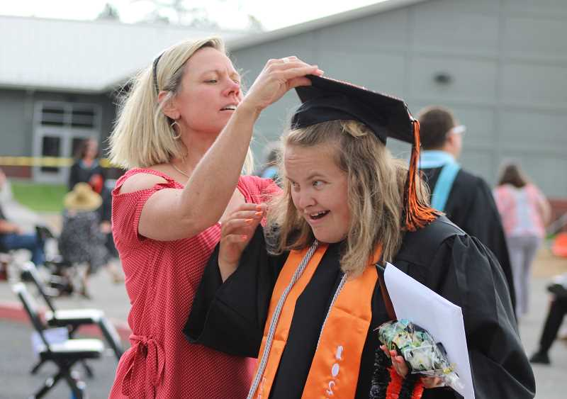 PIONEER FILE PHOTO  - Culver High School seniors will graduate during an outdoor ceremony on the athletic field Saturday, June 5. Tickets will be required for guests. Pictured, a 2020 graduate gets help with her cap.