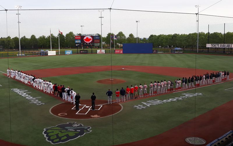 PMG PHOTO: MARK MILLER - The Vancouver Canadians, left, and the Spokane Indians, right, line up for the playing of the national anthems before a Tuesday, May 11, game at Ron Tonkin Field in Hillsboro.