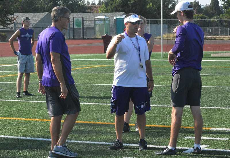 PMG FILE PHOTO - Sunset offensive coordinator Dominic Ferraro (center) talks with coaches at Sunset High School. Ferraro was hired at Forest Grove High School as the new head football coach Wednesday, May 13.