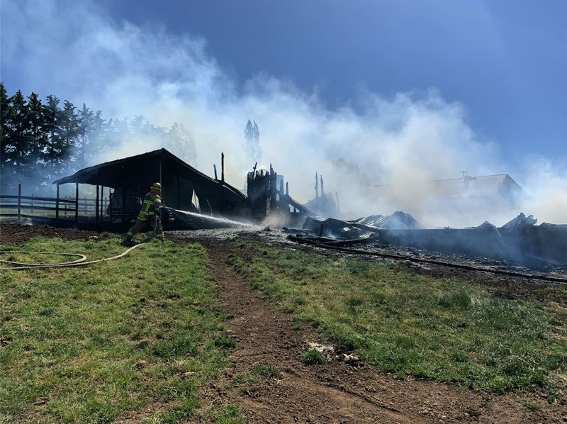 COURTESY PHOTO: TUALATIN VALLEY FIRE & RESCUE - A firefighter extinguishes hotspots from a barn fire in rural Sherwood on Friday, May 14.