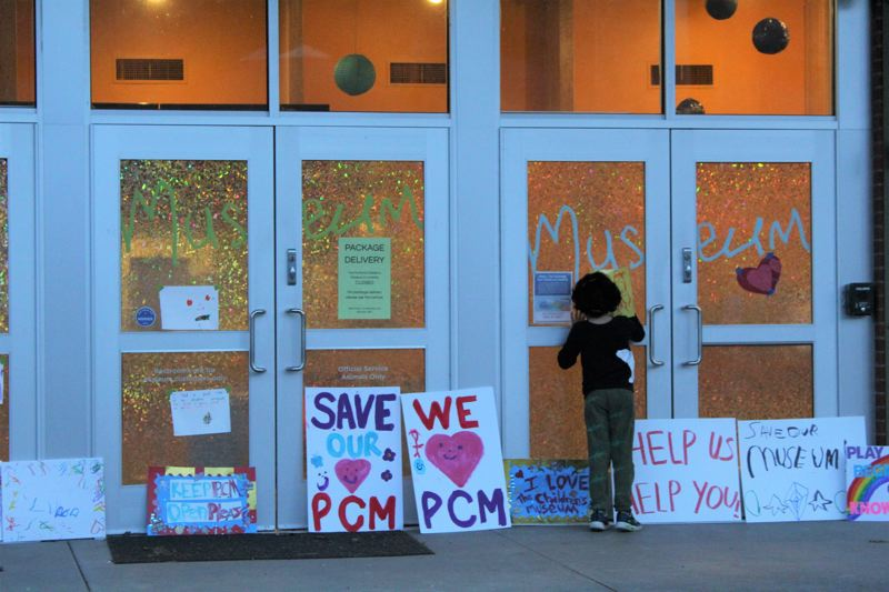 PMG PHOTO: COURTNEY VAUGHN - A child peers through the doors of the shuttered Portland Childrens Museum.