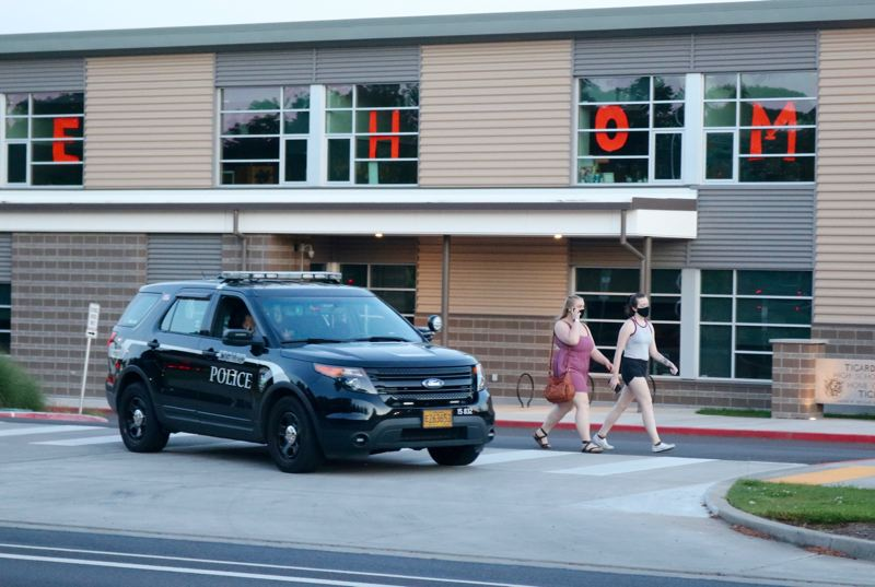 PMG PHOTO: ZANE SPARLING - Pedestrians walk past Tigard High School as a Tigard Police Department squad car monitors a protest across Southwest Durham Road on Sunday, May 16.