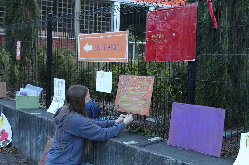 PMG PHOTO: COURTNEY VAUGHN - Emily Reid hangs a sign on a fence at the Portland Childrens Museum during a rally in late March. Parent organizers now say they've ceased efforts to revive the museum.