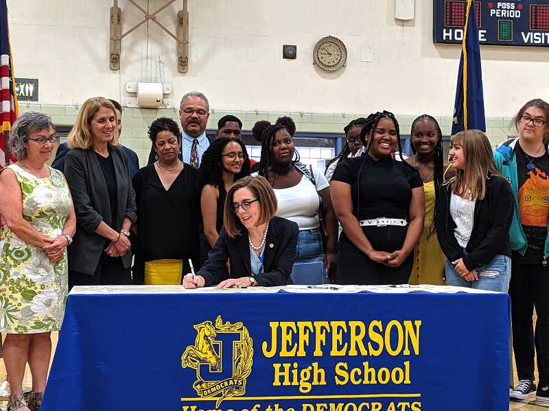 PMG PHOTO: COURTNEY VAUGHN - Gov. Kate Brown adds her signature to the Student Success Act in the presence of staff, students and Portland school board members at Jefferson High School., Portland Tribune - News Gov. Kate Brown visits Portland high school to sign 'game changer' Student Success Act  Oregon's governor welcomes students back to school with $2 billion in education funding