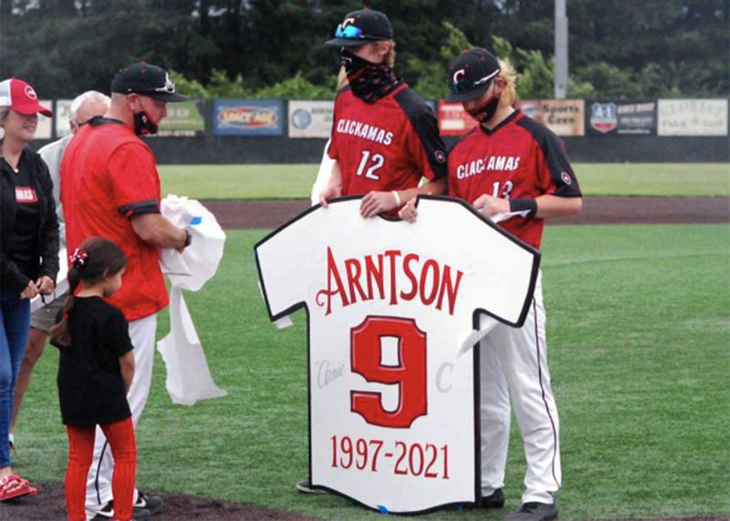 COURTESY PHOTO: OSAATODAY - Clackamas seniors J.D. Dorn (no. 12) and K.C. Miller hold up coach John Arntson's retired jersey as Arntson (left) prepares to coach his last home game.