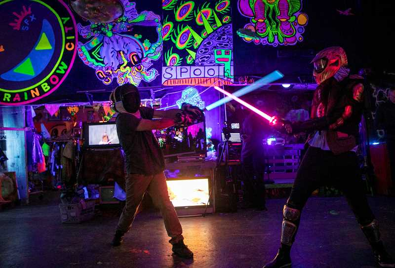 PMG PHOTO: JAIME VALDEZ - At Sword Society on Tuesdays at Rainbow City in Portland, anyone can duel with light sabers while a DJ (in the rear, at right) plays dance music. Players store their weapons in golf bags. Sabers range in value from $100 to $400. Club organizers sometimes film the fights with a 360-degree camera and replay the surreal videos.