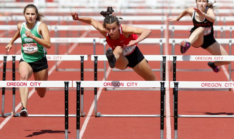 PMG PHOTO: JONATHAN HOUSE - Oregon City junior Harley Daniel races to victory in the 100-meter high hurdles while leading the Pioneers to victory in the Oregon 6A Track and Field State Showcase on Saturday, May 22, at Oregon City's Pioneer Stadium.