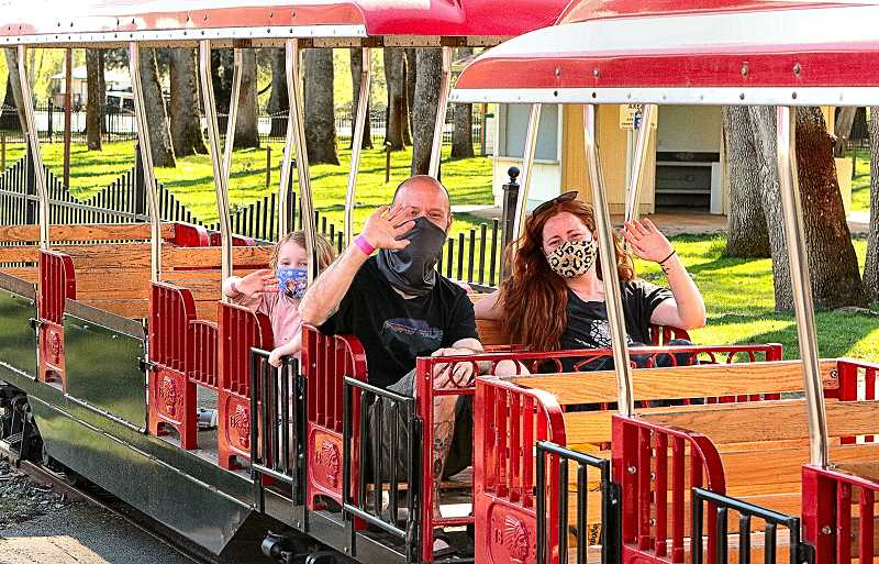 DAVID F. ASHTON - Piper Cook, riding behind her parents, Matt and Stacy Cook, came all the way from Sweet Home, south of Salem, to have a fun family day at the newly-reopened Oaks Amusement Park.