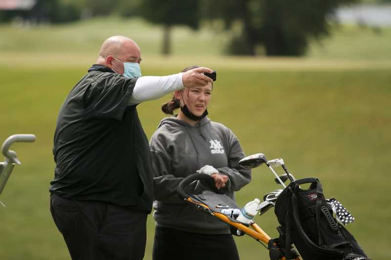PMG PHOTO: PHIL HAWKINS - North Marion coach Terry McCullough provides a few last-minute pointers before Lana Shevchenko tees off on the opening hole at Trysting Tree. Shevchenko went on to tie  her personal record with a 25th-place score of 102, helping the Huskies place seventh at the state showcase.