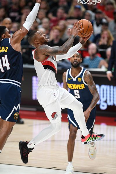 PMG FILE PHOTO - Portland Trail Blazers guard Damian Lillard drives to the hoop during an October 2019 NBA game against the Denver Nuggets at the Moda Center. On Thursday, May 27, the Blazers clash again with the Nuggets, this time with vaccinated fans welcome.