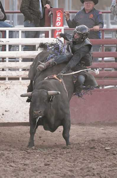 CENTRAL OREGONIAN - Parker Buchanan, of Powell Butte, tries to hang on during a bull ride at the prep rodeo in Prineville earlier in the season.