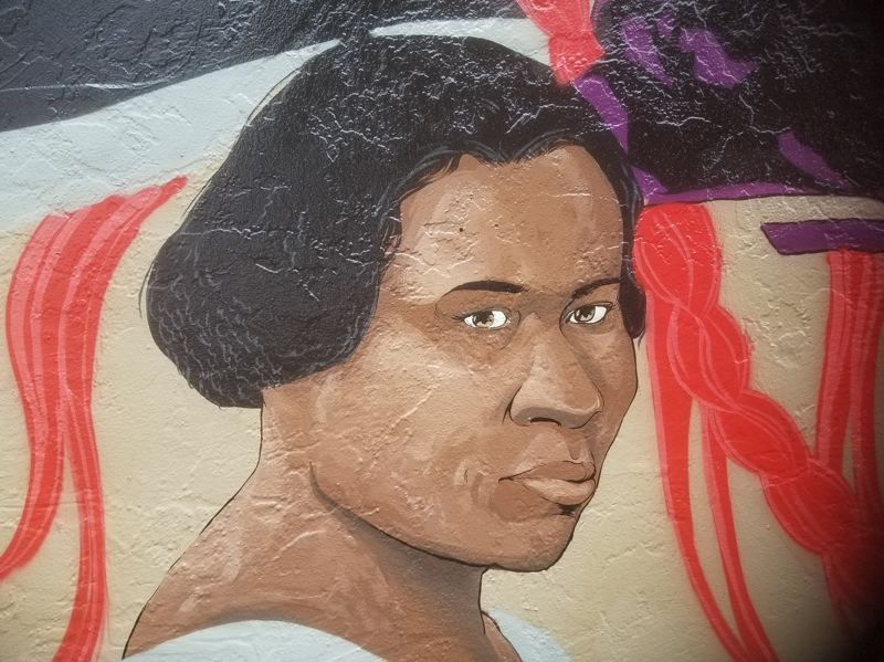 PMG PHOTO: CHRISTOPHER KEIZUR - Kashi Pasaye removed graffiti that had covered the eyes of Madam C.J. Walker and marred the Hairitage mural.