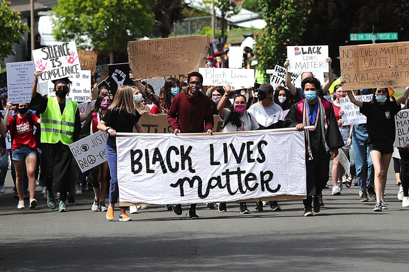 PMG FILE PHOTO: JAIME VALDEZ - Abdi Mohamoud (center), Sarah Gentry (left) and Matt Brown (right) lead a march through a Tualatin neighborhood on June 11 along the way to Tigard High School. The group of 400 marchers were part of the Student March for Black Lives.
