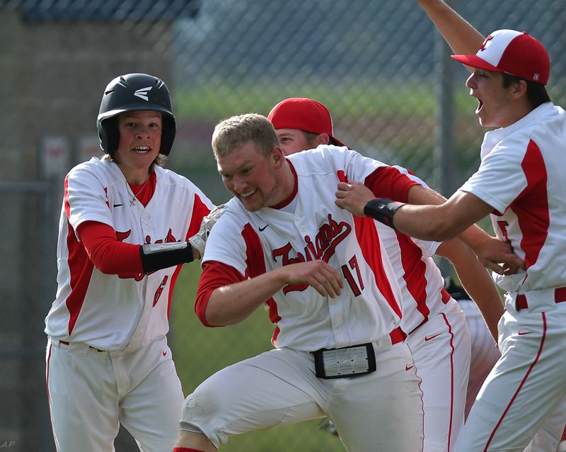 COURTESY PHOTO: ANDRE PANSE - The Kennedy baseball team celebrates around senior Cole Boen (17) in the teams 2-1 victory over Dufur on May 18, propelling the Trojans into the championship double-header on May 22.