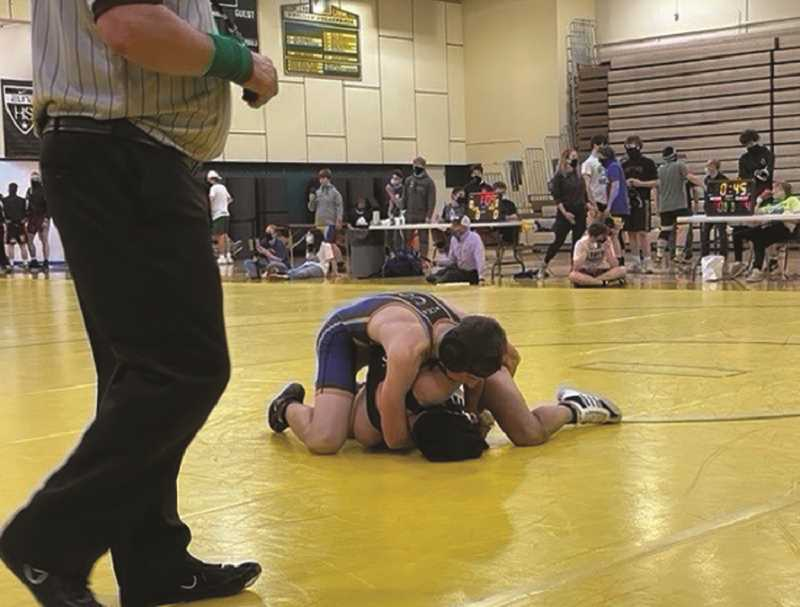COURTESY PHOTO - Canby freshman Craig Williams works for a cradle against his David Douglas opponent. Williams would go on to win the bout 4-2.