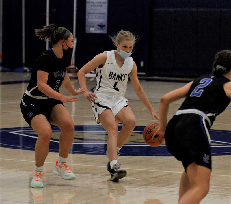 PMG PHOTO: WADE EVANSON - Banks' Kate Hailey dribbles around a Valley Catholic defender Josie Napoli during the Braves' game against the Valiants Thursday night, May 27, at Banks High School.