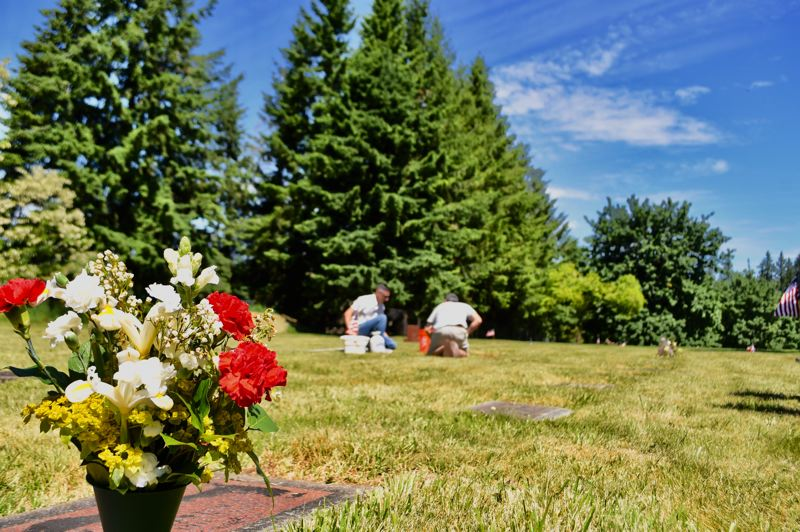 PMG PHOTO: BRITTANY ALLEN - Many graves at Fir Hill Cemetery in Sandy received fresh flowers and decoration for Memorial Day, and some were tended to with a wash and scrub by loved ones.