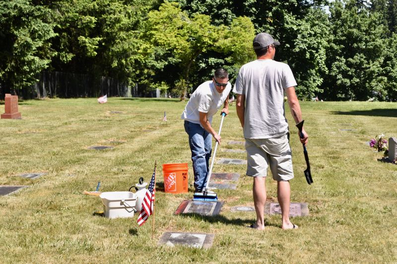 PMG PHOTO: BRITTANY ALLEN - Two men give a headstone at Fir Hill Cemetery a good scrub in honor of Memorial Day.