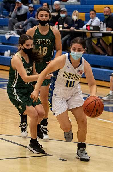 LON AUSTIN - Lauren Papke drives to the bucket against Pendleton. The Cowgirls lost a heartbreaker to the Bucks but then rebounded to beat Redmond 44-33.