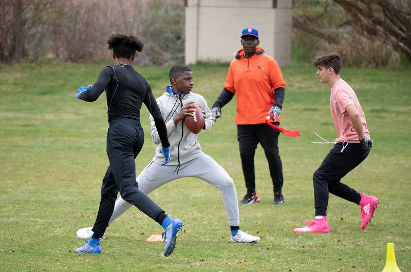 LON AUSTIN - John Charles looks on as California resident Amare Brooks readies to pass during a private quarterback clinic taught by Charles in April. Assiting on the day were Crook County High athletes Kyree Willis, left, and Cameron Carr. Charles has operated a clinic business for 10 years.