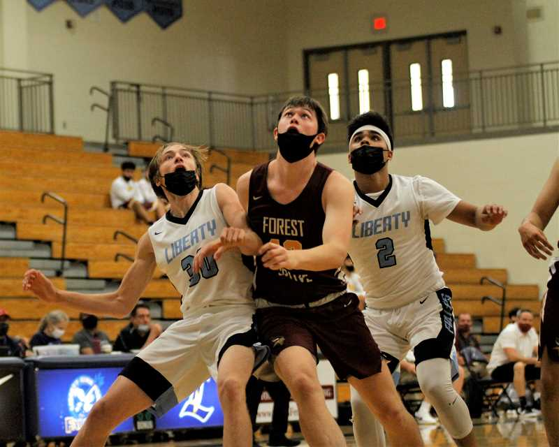 PMG PHOTO: WADE EVANSON - Forest Grove's Braden Hudgins battles for a rebound with Liberty's Xanden Unciano (2) and John Marugg (30) during the teams' game Tuesday, June 1, at Liberty High School.