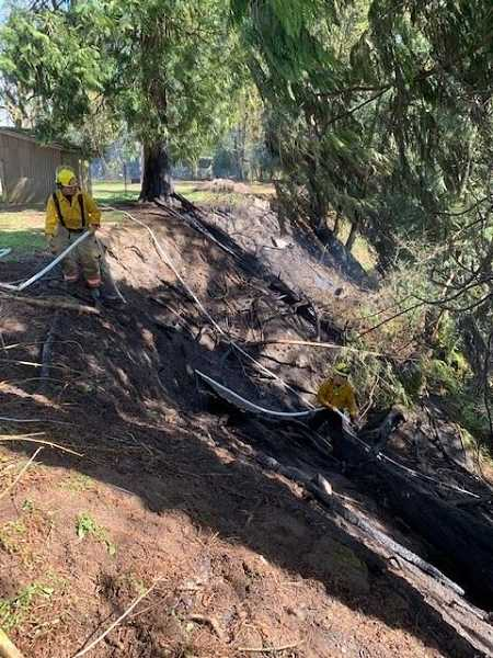 COURTESY PHOTO: CANBY FIRE - Fire crews fight a brush fire on steep terrain on April 13 in Canby.