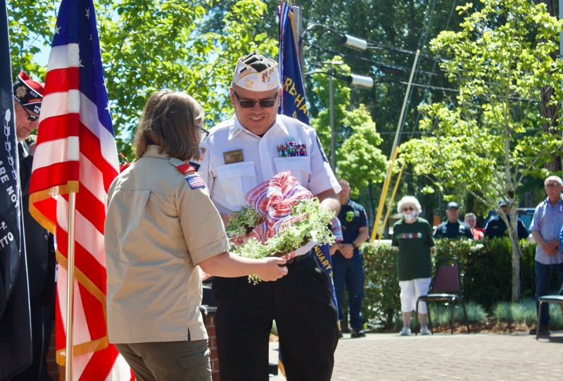 PMG PHOTO: CHRISTOPHER KEIZUR - Air Force veteran Frank West accepts a wreath during a ceremony at the Gresham Heroes Memorial.