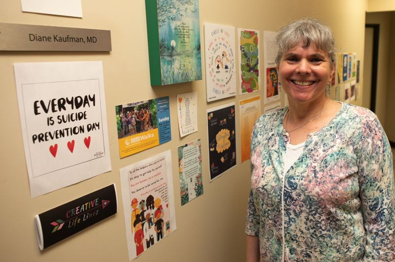 PMG PHOTO: JAIME VALDEZ - Dr. Diane Kaufman stands outside her office at Mind Matters PC in Hillsboro among inspirational posters and other works of art she has produced as part of her art therapy psychiatric work.