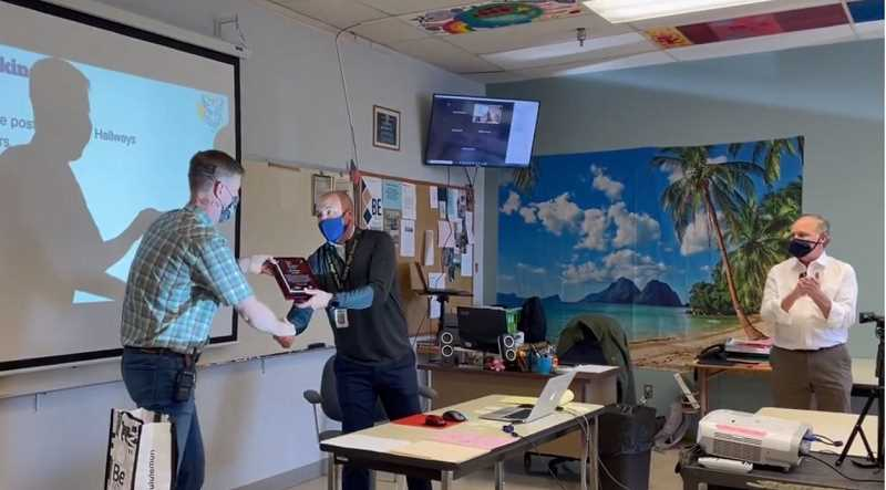 COURTESY PHOTO - Canby High School Principal Greg Dinse hands leadership teacher JD Bellum the CARE Award. Superintendent Trip Goodall is pictured at right.