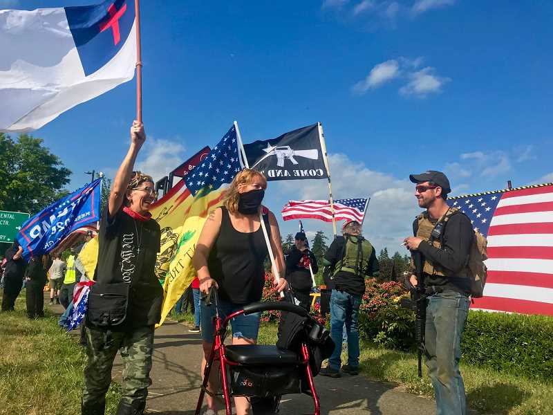 PMG PHOTO: ZANE SPARLING - A man with a rifle stands watch during a flag wave rally organized along Higway 213 in Oregon City on Friday, May 21, one of the two flag wave events Larry Didway referenced in his letter.