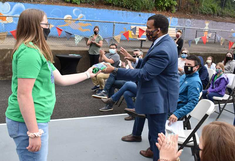 PMG PHOTO: RAYMOND RENDLEMAN - Girl Scout Kate Buehrig at the June 5 eventpasses a symbolic 'torch' of stewardship, in the form of a rolled-up Latourette Park T-shirt, to Oregon City Parks Director Kendall Reid.