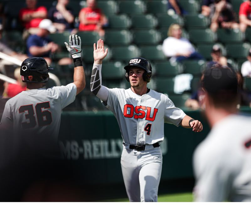 COURTESY PHOTO: MARIO TERRANA/OSU ATHLETICS - Justin Boyd gets a high-five after scoring a run as OSU led 5-0 early only to lose to Dallas Baptist, 8-5.
