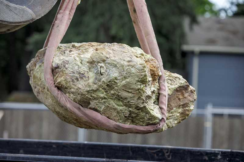 PMG PHOTO: JONATHAN HOUSE - The boulder is moved onto a truck that was taking it to the Tualatin Heritage Center.
