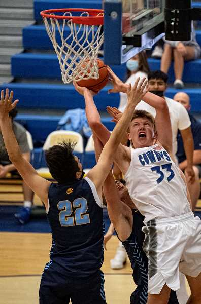 LON AUSTIN - Cayden Lowenbach powers to the hole against Bend. The 6-6 post scored 14 points in the victory. He and guard Kevin Sanchez provide an inside-outside attack that has pushed the Cowboys to 9-0 this season.