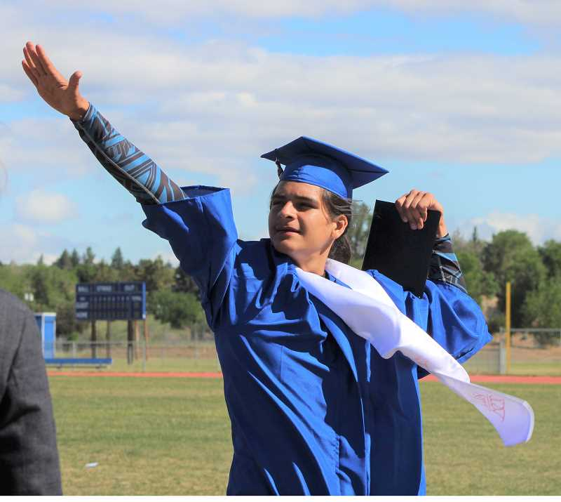 HOLLY SCHOLZ/MADRAS PIONEER  - Bridges High School graduate Jeremiah Zacarias celebrates with the dab after getting his diploma during commencement Saturday.