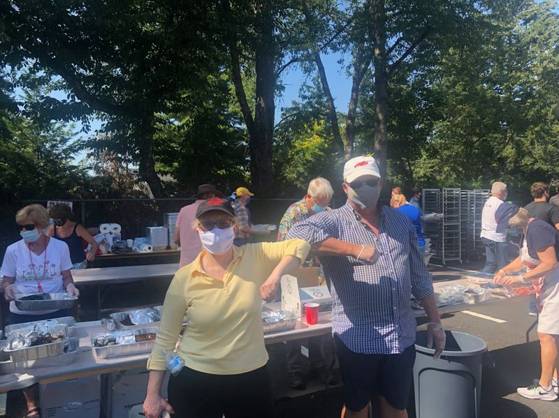 COURTESY PHOTO - Outgoing Rotary Club of Lake Oswego President Nell Diamond, left, and former president Scott Havens volunteer during last year's drive-thru lobster feed.