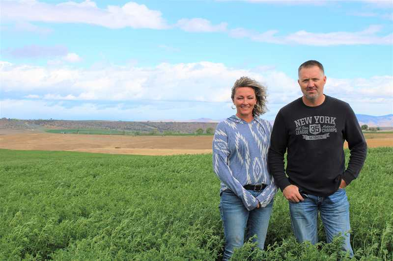 PAT KRUIS/MADRAS PIONEER  - JoHanna and Jeremy Symons own 1,100 acres. This year because of the water shortage, they are able to plant only 500 acres. The rest, like the field behind them, lies fallow, costing them money but producing nothing.