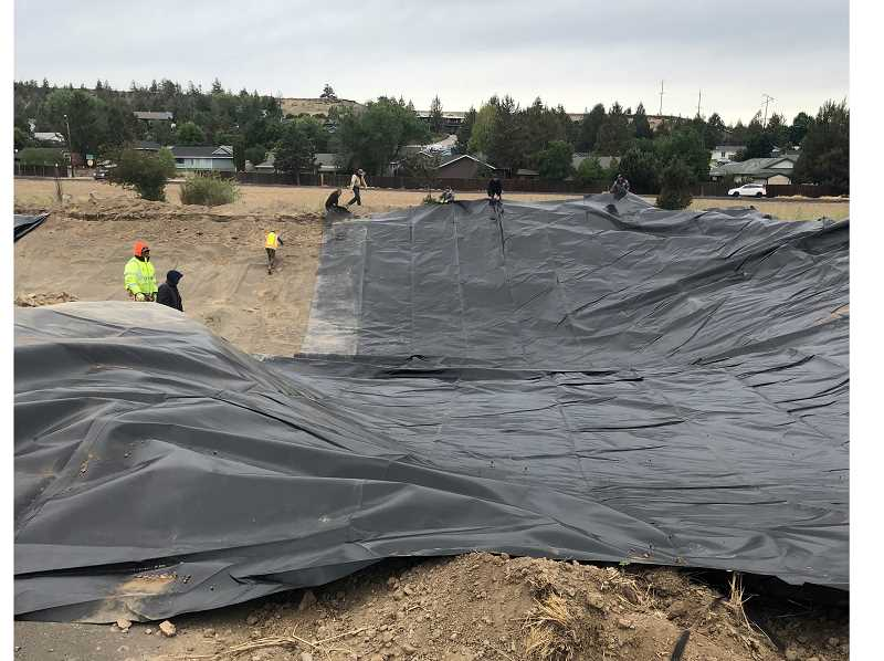 PHOTO COURTESY OF BLAKE FONNESBECK    - Crews help pull the liner at the Jefferson County Fairgrounds fishing pond Monday morning.