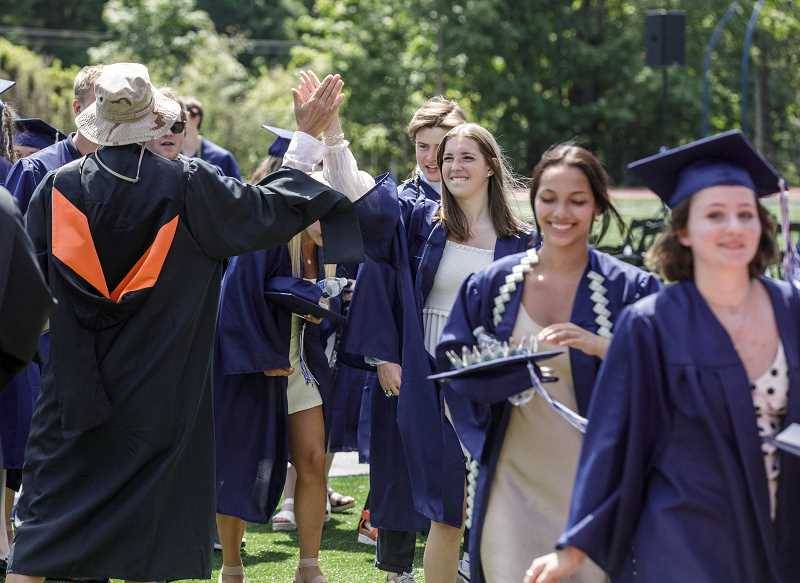 PMG PHOTO: JONATHAN HOUSE - Faculty and graduates high-five after Lake Oswego High's graduation.