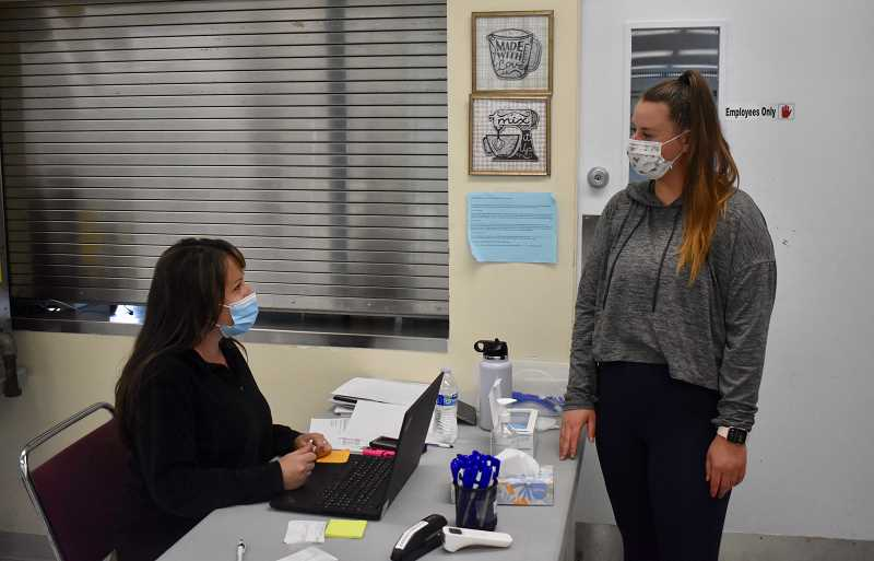 PMG PHOTO: EMILY LINDSTRAND - Checking in is the first step after arrival at COVID-19 vaccination clinics, like the one last month at the Estacada Community Center.