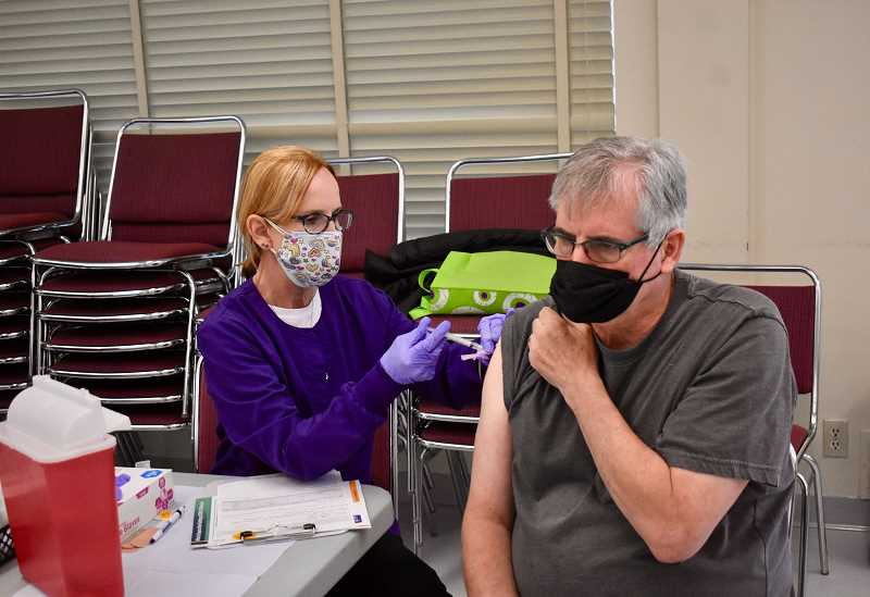 PMG PHOTO: EMILY LINDSTRAND - An attendee of May's COVID-19 vaccination clinic at the Estacada Community Center gets the Johnson & Johnson shot.