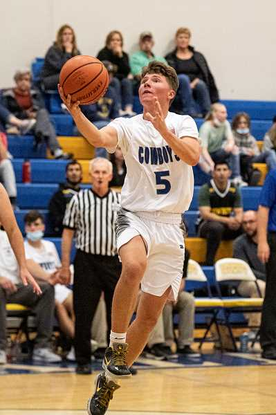 LON AUSTIN - Hogan Smith drives for a layup against The Dalles. The Cowboys, now 12-0 on the season, hammered the Riverhawks 61-44.