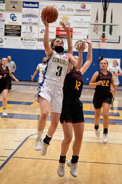 LON AUSTIN - Kaitlynn Weaver takes it strong to the basket during the Cowgirls' 53-41 homecourt victory over Redmond June 10. The Cowgirls, who stand third in the Intermountain Conference, rebounded from a loss against Pendleton to beat both Redmond and The Dalles later in the week.