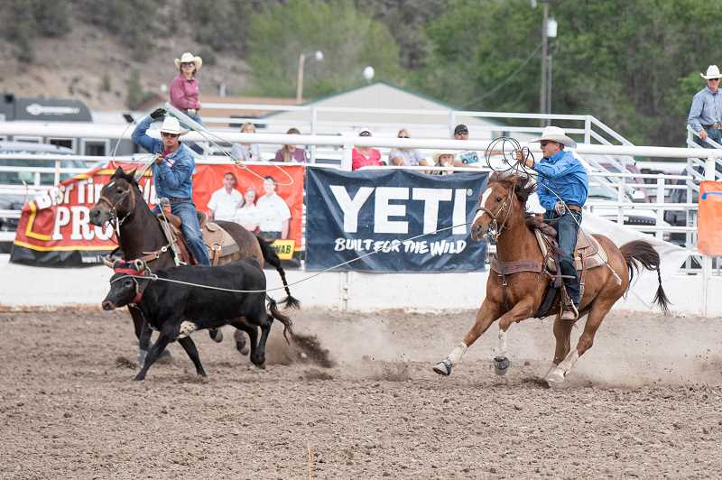 LON AUSTIN - Caleb Carpenter, left, of Powell Butte preps to throw a rope at the heels of a calf during the team roping competition at the Oregon State High School Rodeo Assocation finals in Prineville last week. Carpenter and his partner, Cael Stratton, of Lakeview, dominated the event during the finals and came away as state champions. Powell Butte's Kennedy Buckner also became a state champion, in the goat typing event.