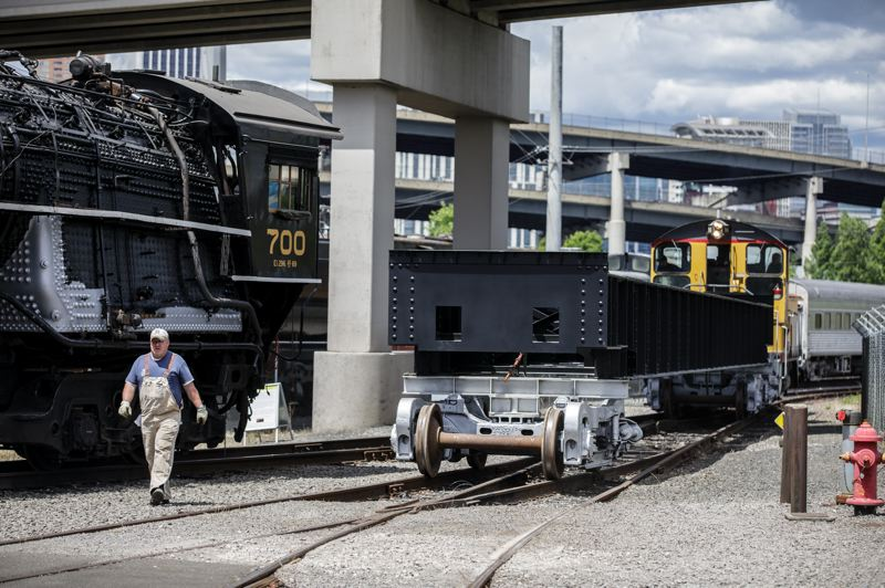 PORTLAND TRIBUNE PHOTO: JONATHAN HOUSE - The 100-foot, 240,000 pound turntable bridge is pushed past the Oregon Railroad & Navigation Co. 197 to the front of the Oregon Rail Heritage Center on June 9.