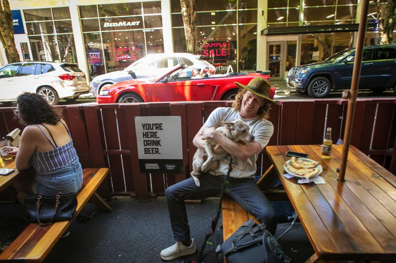"""PMG PHOTO: JAIME VALDEZ - Rusty Shackleford with his dog, Khaleesi, having a was having a slice outside Pizza Schmizza in the Pearl. """"I tend to dine out more than most, and any time I can choose to be outside I'll take it,"""" he said."""