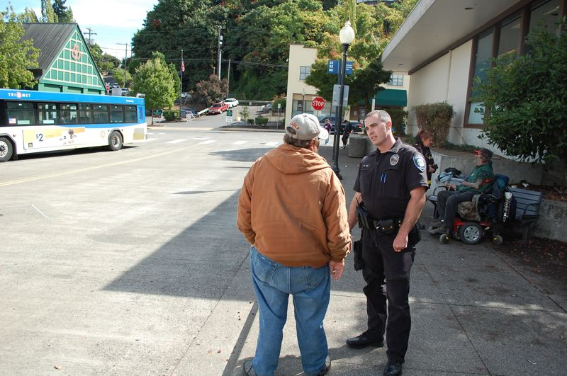 PMG FILE PHOTO: RAYMOND RENDLEMAN - Mike Day, the Oregon City Police Department's former homeless liaison, meets with a man near a TriMet bus stop in 2017.